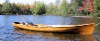 hand built wooden boat that can be propelled with oars or a motor, floating on a lake