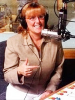blonde woman wearing glasses, headphones and brown jacket seated in a radio booth in front of a silver microphone.