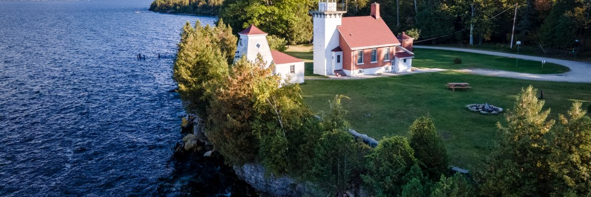 Aerial view of red roofed, white sided lighthouse buildings, surrounded by trees and grass sitting on top of a rocky bluff over the water