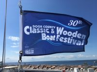 """small blue flag with words """"30th Door County Classic & Wooden Boat Festival"""" and Door County Maritime Museum logo, flying in the wind with Green Bay in background"""