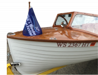 Classic wooden boat, with white boards on bow, varnished wood on deck top, and blue Classic & Wooden Boat Festival flag flying from the bowpole
