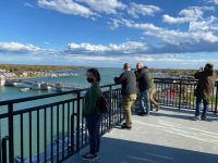 4 adults standing and leaning against a black metal railing, blue sky with white clouds, overlooking Sturgeon Bay bridges and water. Fall colors on trees