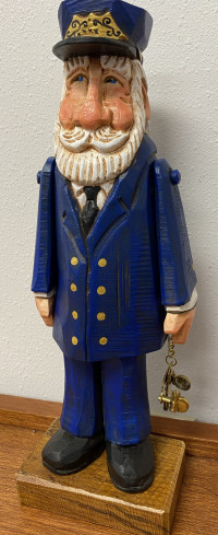 Hand carved wooden figure of a man with white beard, dressed in blue boat captain's suit, holding a to scale brass sextant
