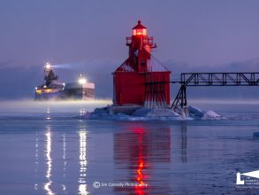 Freighter with two lights on navigating by the red Sturgeon Bay Pierhead Lighthouse, which is reflecting on the winter ice