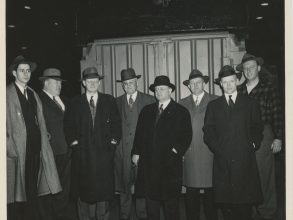 Group of 8 men wearing long coats and fedora hats, standing in front of a shipping container prototype