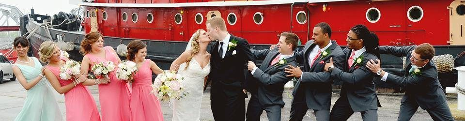 Bridal party in in front of red tug boat. Women in pink dresses, men in black tuxedos pretending to 'tug' on the bride and groom.